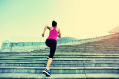 Woman running up on mountain stairs Royalty Free Stock Images