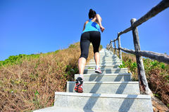 Woman running up on mountain Stock Images