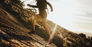 Woman running up a rocky mountain slope. Cropped shot of female trail runner running uphill on a sunny day royalty free stock image