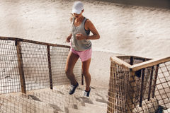 Woman running up the staircase on beach Royalty Free Stock Photography