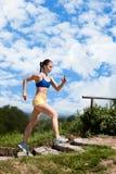 Woman running up stairs Stock Photo