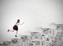Woman running up stairs in concrete wall. Businesswoman is running up the stairs in concrete wall. Startup icons are drawn with marker under it. Concept of Royalty Free Stock Photo