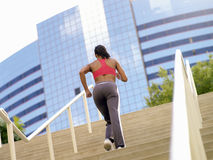 Woman running up stairs, rear view (tilt) Stock Image