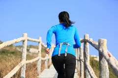 Woman running up to mountain peak Royalty Free Stock Photography