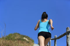 Woman running up to mountain peak Royalty Free Stock Image