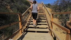 Woman running up wooden stairs by mountains stock video footage