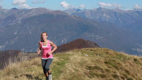Woman running uphill on mountain trail stock video footage