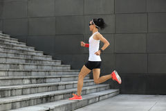 Woman running upstairs on city stairs Stock Photography