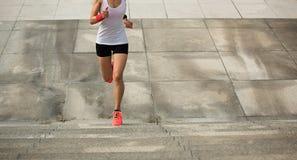 Woman running upstairs on city stairs Stock Photo
