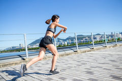 Woman running and using wearable watch in city Royalty Free Stock Image