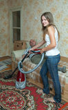 Woman running the vacuum cleaner at home. Yang womam doing housecleaning and man resting over sofa royalty free stock photos