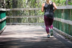 Woman Running on Walkway in the Park in a Hot Day. On Blur Background. Turkey Creek, Niceville, Florida stock images