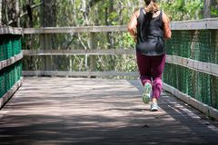Woman Running on Walkway in the Park in a Hot Day. On Blur Background. Turkey Creek, Niceville, Florida royalty free stock photography