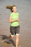 Woman running in water. A woman wearing green running bare foot in the water Royalty Free Stock Images