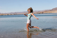 Woman running in water Stock Photo