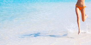 Woman running in water. A view of the legs and midsection of a woman, running through shallow water at a beach Stock Photos