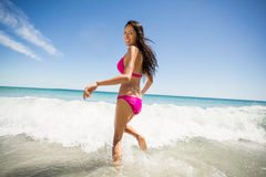Woman running in water Stock Images