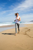 Woman running in white shirt on a beach Royalty Free Stock Images