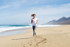 Woman running in white shirt on a beach Royalty Free Stock Image