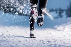 Woman running in winter. Athlete woman is running during winter training outside in cold snow weather Royalty Free Stock Photos