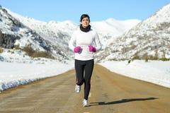 Woman running on winter road Stock Photo