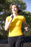 Woman running in yellow shirt. A woman running in the outdoors Stock Image