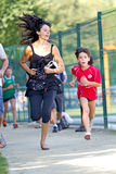 Woman running beside a young boy. Stock Images