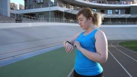 Woman runnner choosing options on fitness bracelet