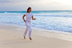 Woman runs  along sea coast.portrait to the utmost Royalty Free Stock Image