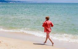 Woman runs along the seashore Stock Images