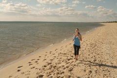 Woman runs along water Royalty Free Stock Image