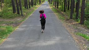 Woman runs through the forest. Healthy lifestyle concept stock video