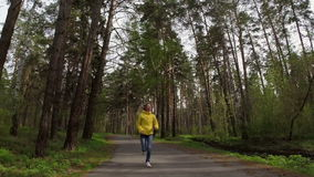 Woman runs on the forest road. Slow motion. The woman runs on the forest road. Slow motion stock footage
