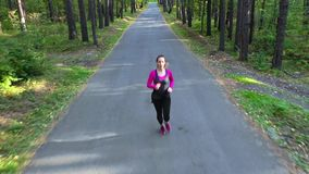 Woman runs through the forest on a straight road. Young woman runs through the forest stock footage