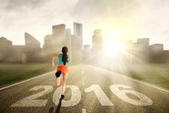 Woman runs on the highway with numbers 2016 Royalty Free Stock Photography