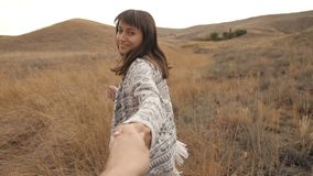 Woman runs holding a man`s hand. At field in slow motion stock video footage