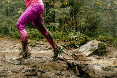Woman runs over rocks. In forest legs in spray dirt Royalty Free Stock Photography