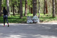Woman runs into park next to plastic bags full of waste. Plastic pollution on environment. Woman does sport in the forest. stock images