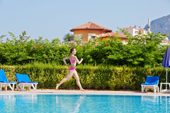 Woman runs at poolside around pool. Young woman runs at poolside around pool Royalty Free Stock Photography