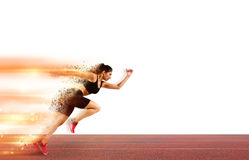 Woman runs in a race to the stadium. Athletic woman runs in a sport competition with lights trails on the stadium track Royalty Free Stock Images