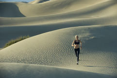 Woman runs on sand dunes Stock Image