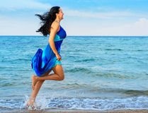 The woman runs on sea coast Royalty Free Stock Photos