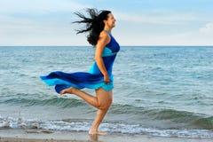 The woman runs on sea coast Royalty Free Stock Photo