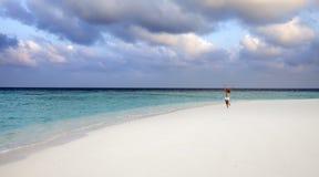 The woman runs on sea coast, Maldives Stock Image