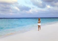 The woman runs on sea coast, Maldives Royalty Free Stock Images