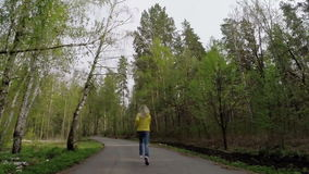 The woman runs. Slow motion. The woman runs on the forest road. Slow motion stock footage