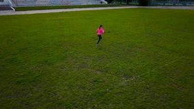 Woman runs through the stadium at sunset, view from the top stock video footage