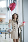 Woman runs to camera holding heart shaped balloon and gift Royalty Free Stock Photo