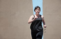 Woman runs to keep in shape Royalty Free Stock Images