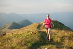 Woman runs on a top of the mountains with mountain range in back royalty free stock photos